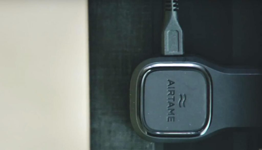 Image of Airtame 1 device plugged into a TV