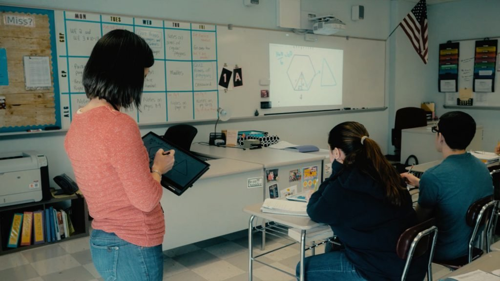 Teacher presents her drawings from her laptop to a screen in front of her class