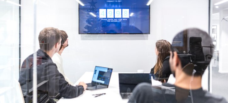 A group of people in a meeting room presenting wirelessly using Airtame