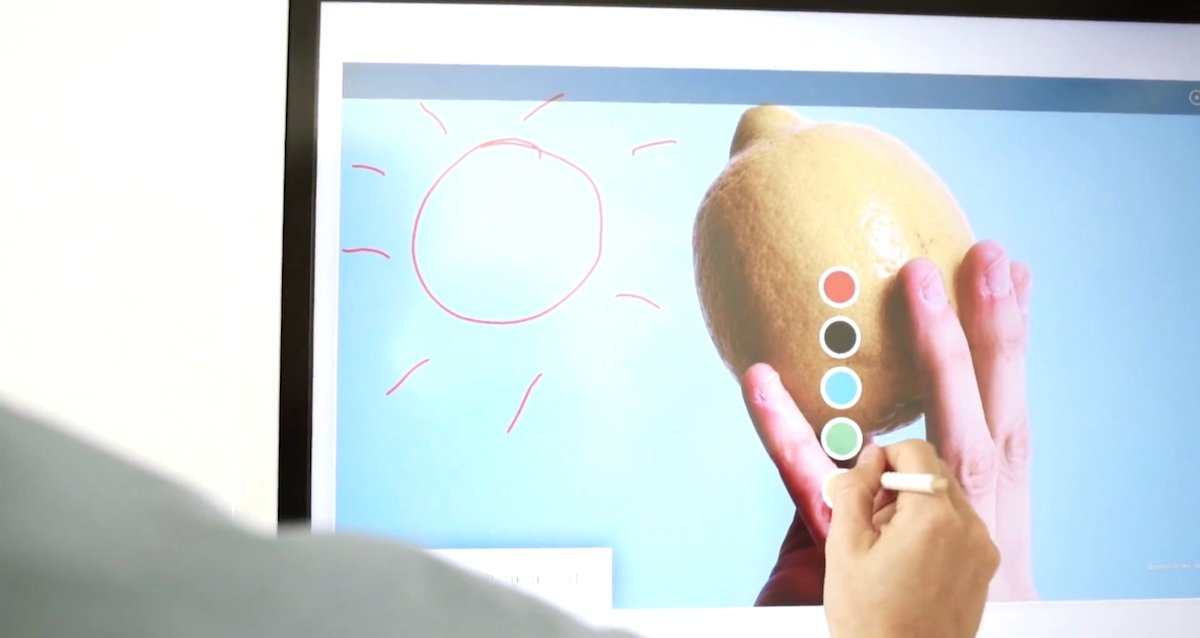 A Samsung Flip screen showing a person drawing on the interactive display