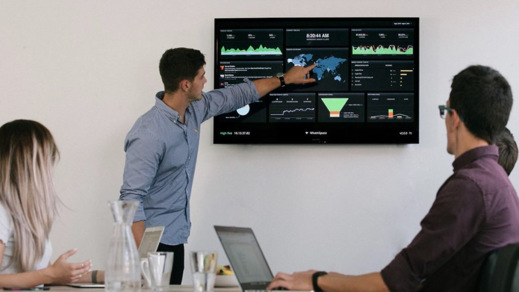 A group of people in a business meeting looking at a screen showing performance dashboards